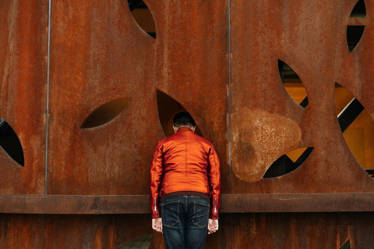 Rear view of man standing against orange rusty wall
