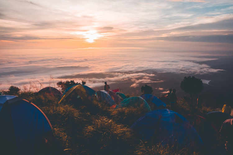 Tents on mountain peak against sky during sunset