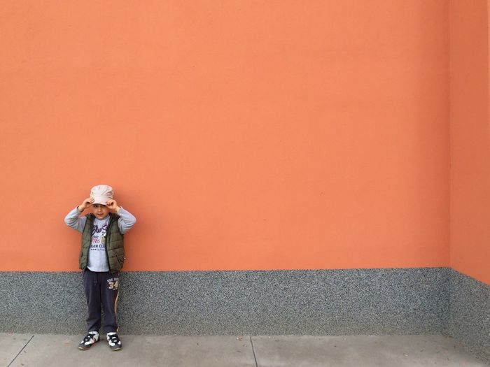 Full length of cute boy standing against wall