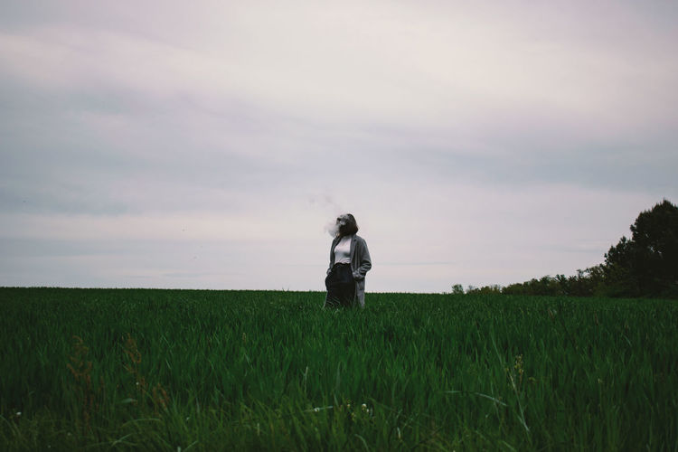 Woman standing amidst crops on agricultural field against sky