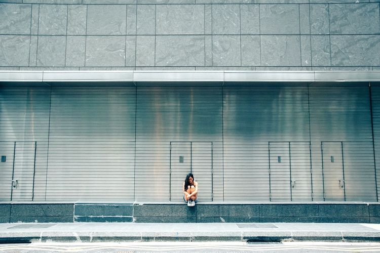 Sad woman sitting against building