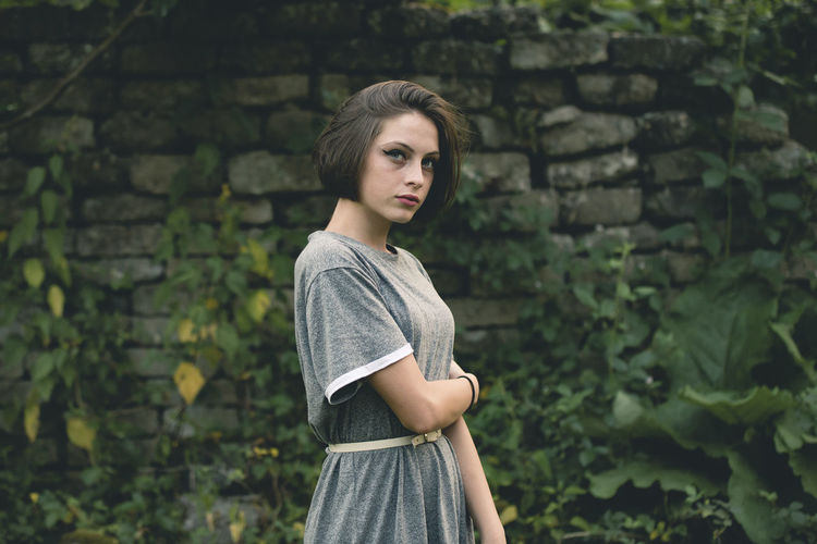Young woman looking away while standing against wall