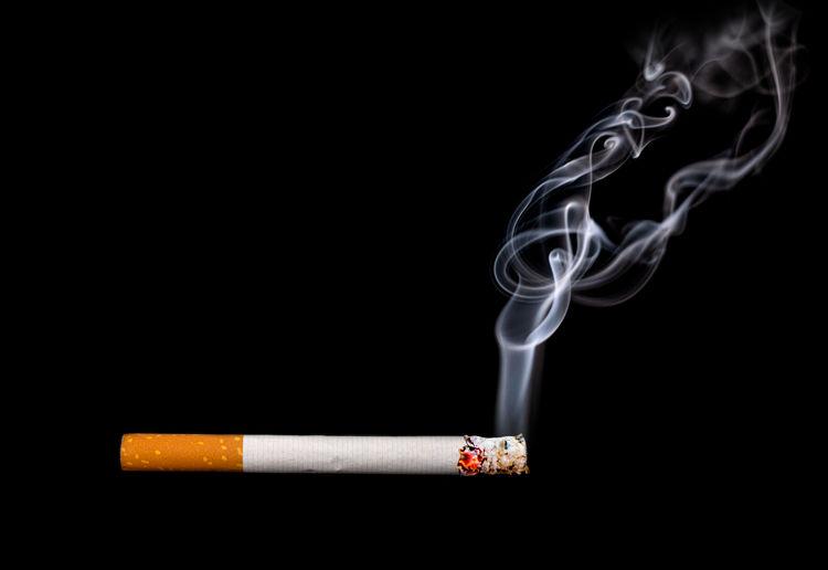 Close-up of burning cigarette against black background