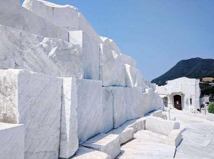 Low angle view of marble structure against clear blue sky