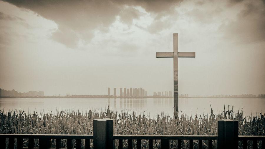 Cross On Lake Against Sky