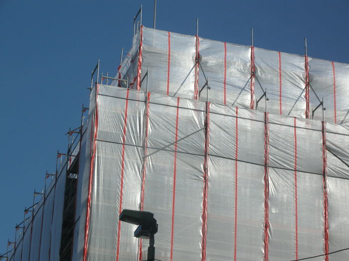 Low angle view of incomplete building against clear blue sky at construction site