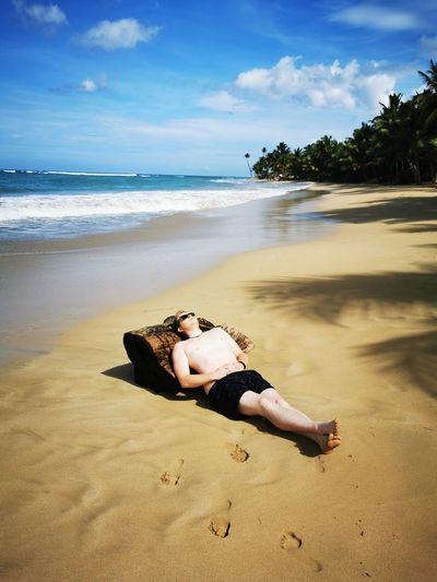 Man lying down on sand at beach against sky
