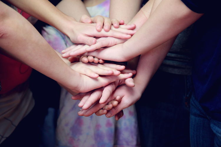 Midsection of children stacking hands