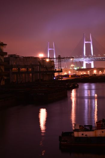 Illuminated yokohama bay bridge over sea against sky