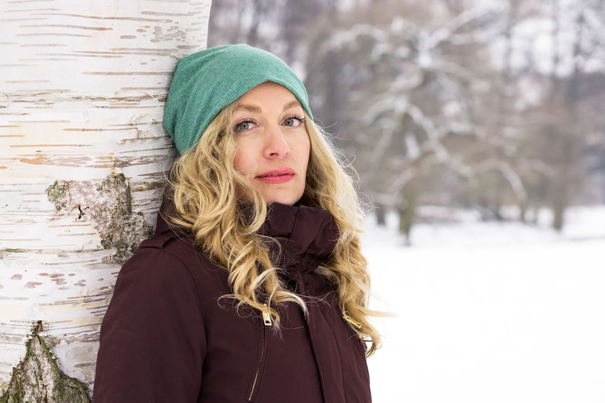 Copy Space Nature Woman Adult Beautiful Woman Blond Hair Cold Temperature Day Female Knit Hat Leaning Against Tree Leisure Activity Long Hair Looking At Camera One Person Outdoors Portrait Real People Snow Warm Clothing Winter Winter Wonderland