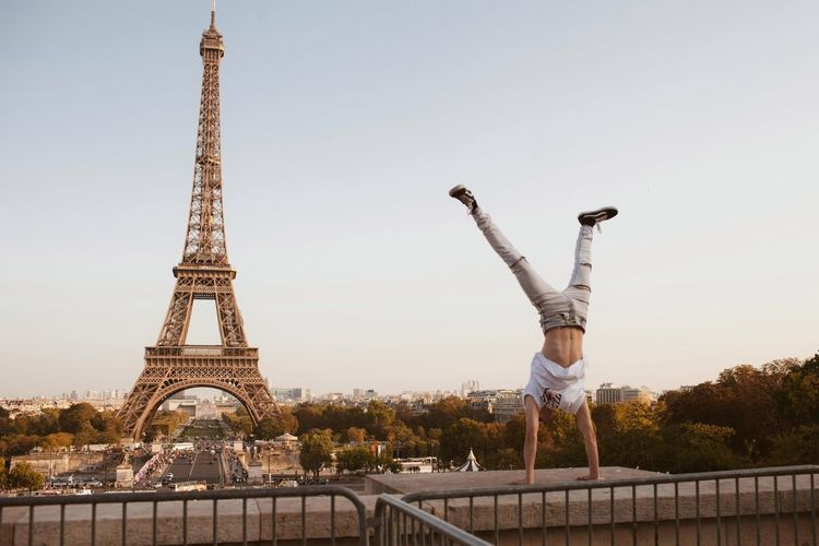 Man doing handstand against eiffel tower