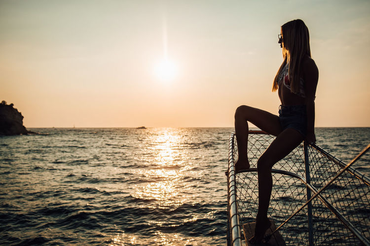 Water Sunset Sky Sea One Person Beauty In Nature Real People Scenics - Nature Lifestyles Leisure Activity Sunlight Nature Tranquility Orange Color Sun Horizon Young Adult Tranquil Scene Idyllic Horizon Over Water Outdoors Hairstyle