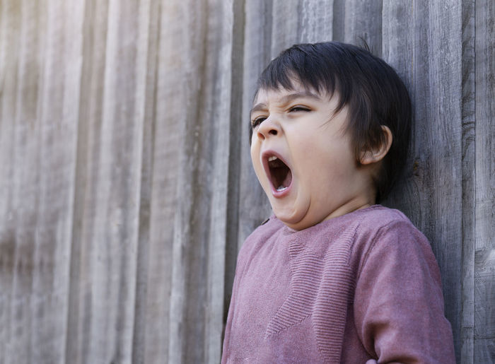 Boy yawning while looking away against wall