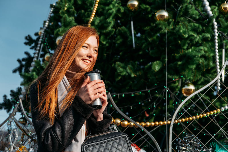 Smiling young woman looking away while holding coffee cup against trees