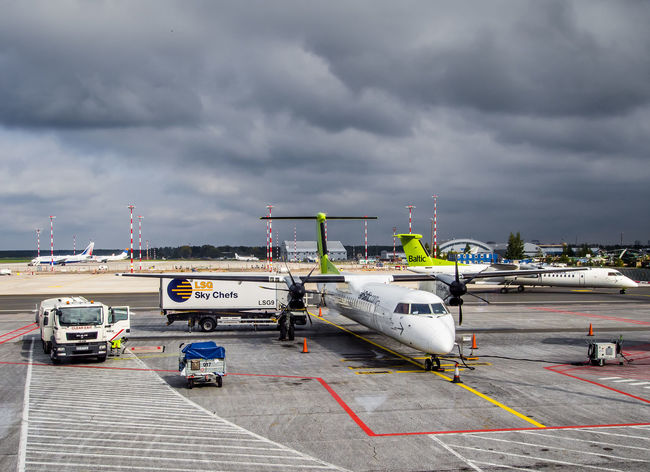Latvia, Riga- September 10, 2014: Preflight service of the plane of airline Airbaltic at the Riga International Airport Dramatic Sky International Latvia Moody Sky Plane Service Transportation Travel Weather Aircraft Airfield Airline Airport Aviation Cloud - Sky Commercial Airplane Departure Editorial  Europe Fueling Preparation  Public Transportation Refueling Riga Technology