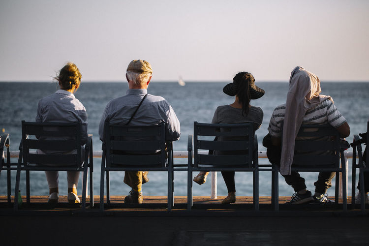 Rear view of people sitting on chair at sea
