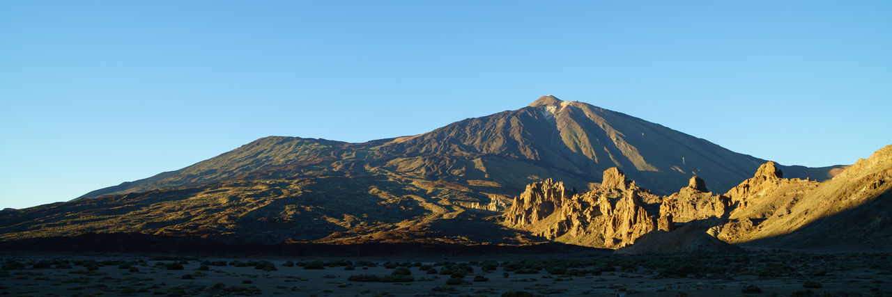 Scenic view of volcanic mountain against clear blue sky - el teide national parc, teneriffa