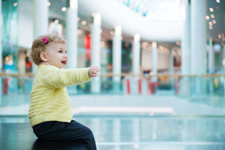 Cute girl sitting at shopping mall
