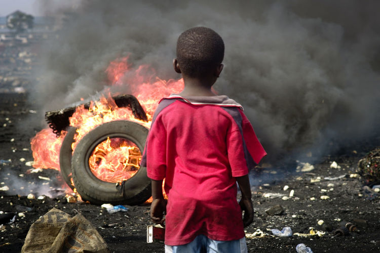 Abogbloshi Accra Africa Black Smoke Burning Child DUMPING SITE E-waste Electronics Industry Environmental Pollution Ghana Harmful Substances Harmful To Health Heat - Temperature Hostile Environment One Person Rear View Waste EyeEmNewHere EyeEmNewHere The Photojournalist - 2017 EyeEm Awards