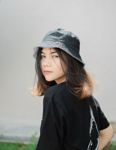 Portrait of young woman wearing hat standing against white background