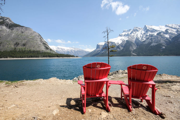 Empty red adirondack chairs at lakeshore against snowcapped mountains