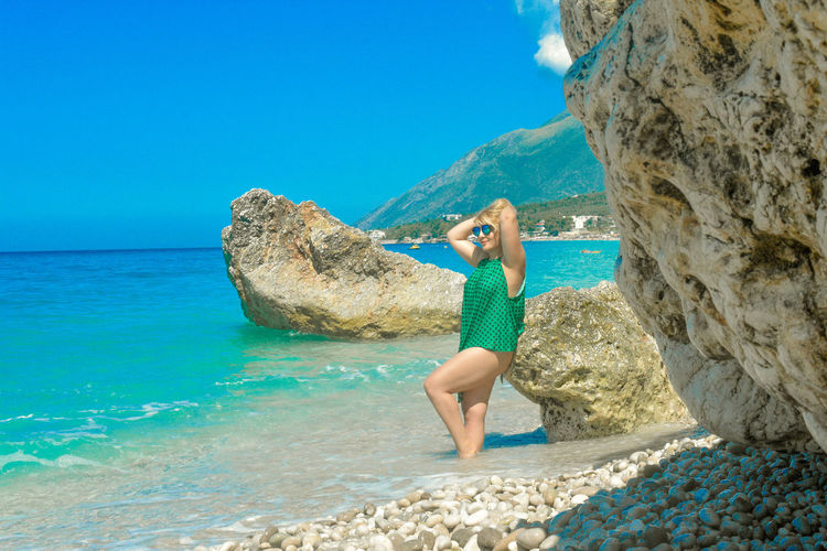 Woman standing by rock at beach