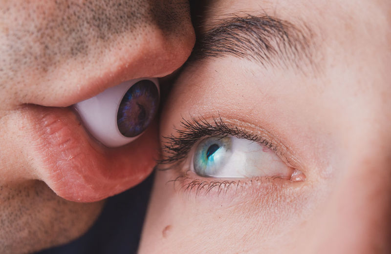 Close-up of woman looking at boyfriend holding artificial eyeball in mouth