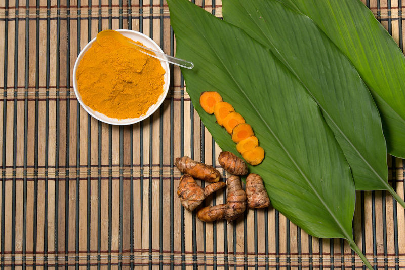 TURMERIC LEAF AND POWDER Pumpkin Leaf Spice Ingredient Directly Above Food And Drink Green Color Turmeric  Indian Food Curry