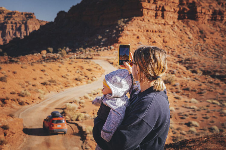 Man photographing woman on rock