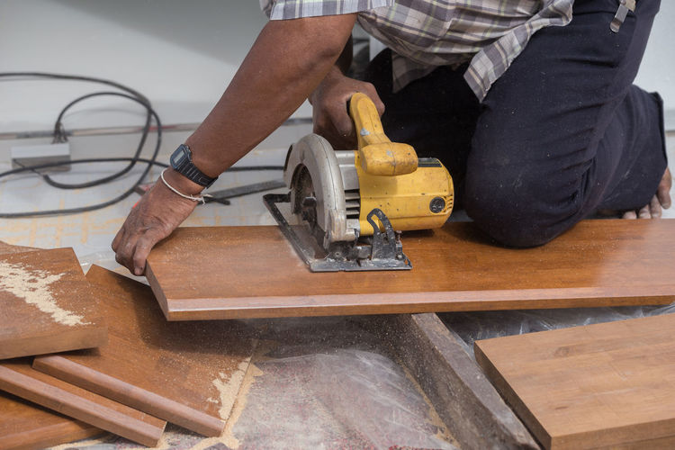 Midsection of man cutting wood