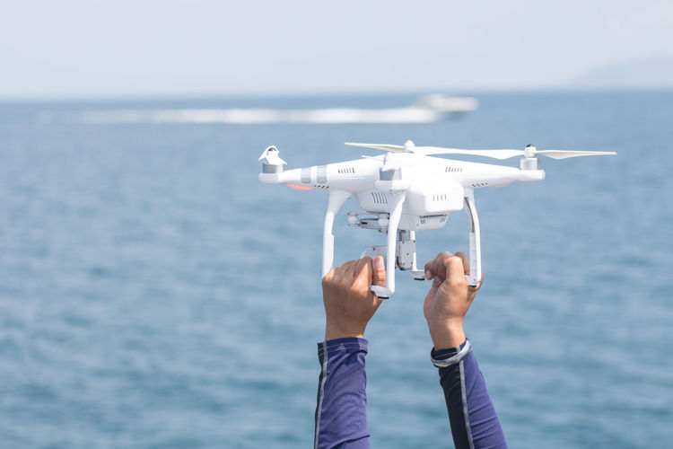 Cropped hands of man holding drone against sea