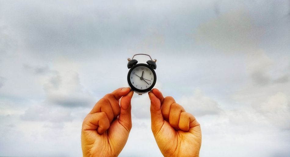 Close-up of cropped hands holding alarm clock against cloudy sky