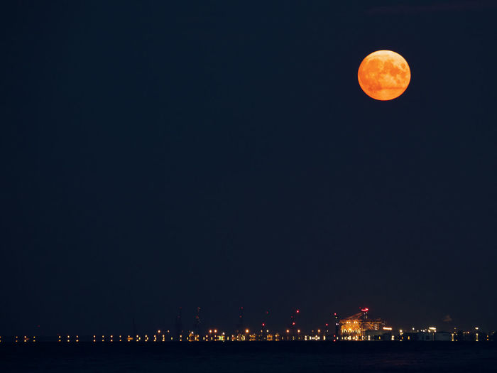 Scenic view of illuminated moon against sky at night