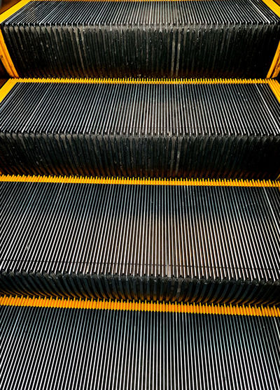 Pattern Full Frame Backgrounds No People Metal Escalator Close-up Indoors  Yellow High Angle View Textured  Day Black Color Staircase Architecture Striped Sunlight Repetition Steps And Staircases Silver Colored