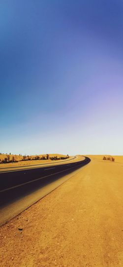 Road by land against clear blue sky