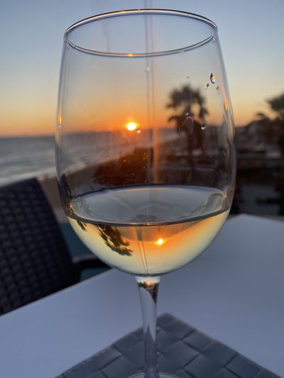 Close-up of beer glass on table against sky during sunset