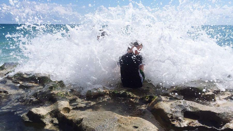 Sea Waves Splashing On Boy Sitting On Rock