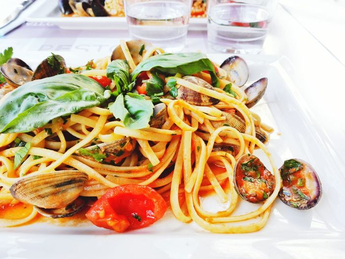 Close-up of noodles with clams in white plate on table