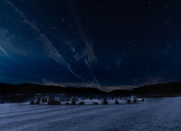 Scenic view of a stone-circle in a field at night under a starry sky.