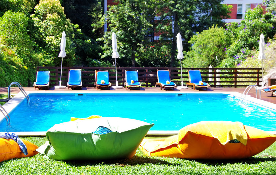 swimming pool with blue water near the garden Grass Green Color Inflatable  Nature No People Outdoors Plant Pool Relaxation Swimming Pool Tree Water