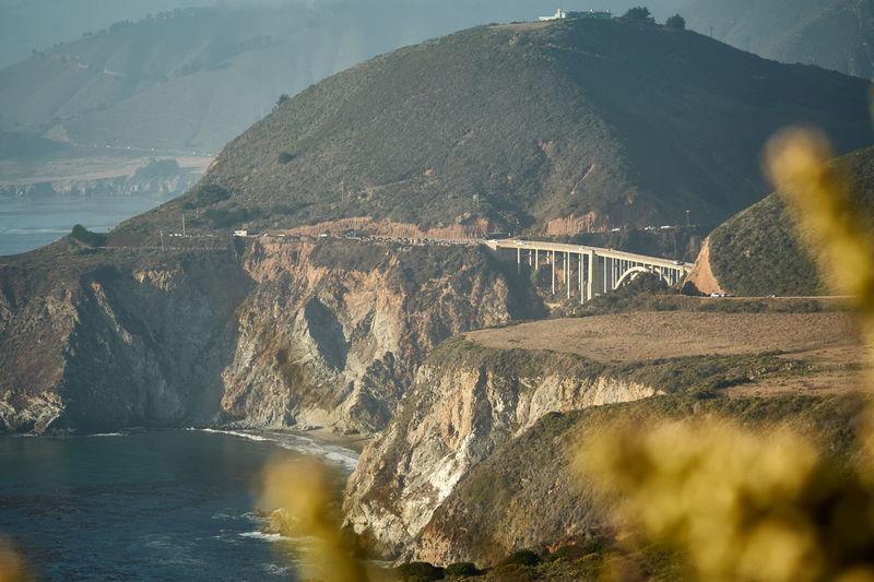 Bridge over river against mountains