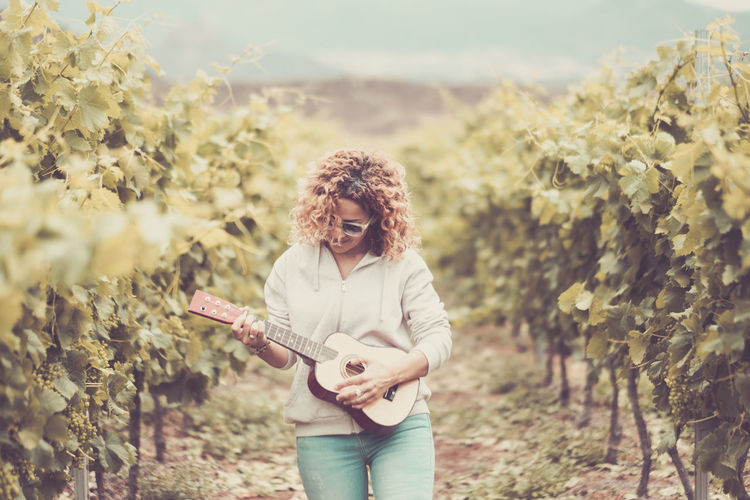 Woman Playing Guitar While Walking Amidst Plants
