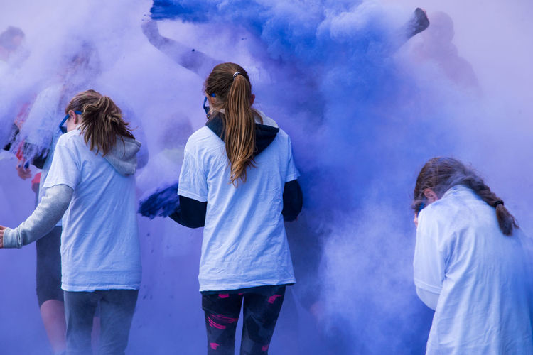 Rear view of teenage girls playing in blue powder paint
