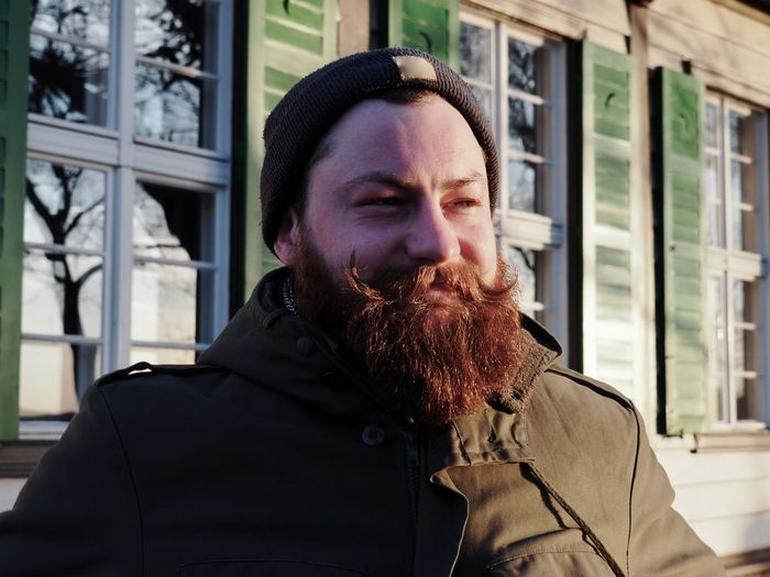 Adult Architecture Beard Clothing Day Facial Hair Headshot Hipster Leisure Activity Lifestyles Lumberjack Males  Mature Men Men Mid Adult Mustache One Person Outdoors Portrait Real People Red Beard Waist Up Warm Clothing Window Young Adult