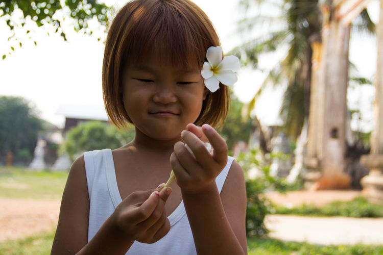 Close-up of cute girl holding flower while standing outdoors