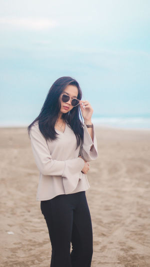 Young woman wearing sunglasses while standing on beach