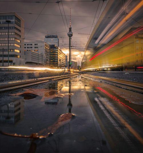Light trails on street in city against sky