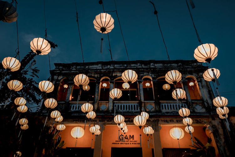 Low angle view of illuminated lanterns hanging by building