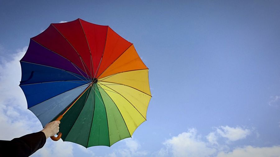Cropped hand holding colorful umbrella against sky