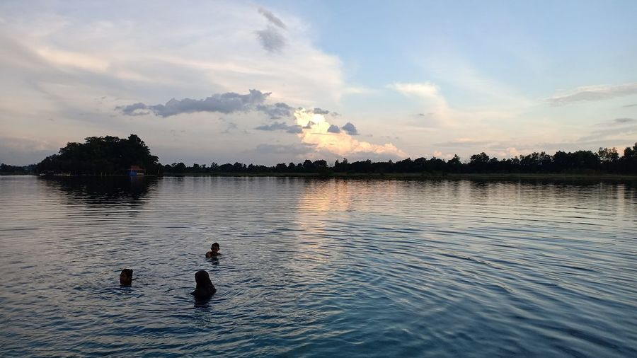 People swimming in lake against sky during sunset